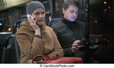 Bus Passengers Using Gadgets - Two passengers are sitting in...