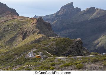 bus runs along a mountain road