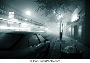 Bus speeding through foggy night street.