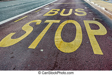 Bus stop sign with yellow paint on asphalt