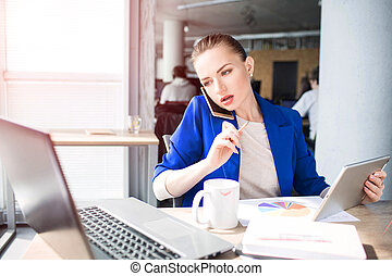 Bus young woman is sitting at the table and talking on the phone. She is looking to laptop's screen. Also gir is holding a tablet in one hand and pen in the other one.