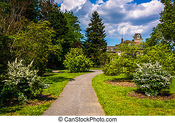 Bushes and trees along a path and the Cylburn Mansion at Cylburn