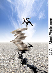 busines and Economic crisis concept. cracked road and unstable businessman on the money tower