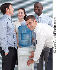 Busines colleagues talking around water cooler in workplace