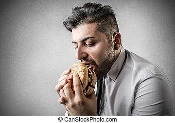 Businesman eating hamburger