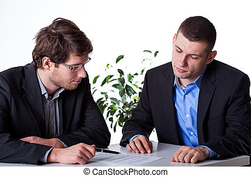 Two smart businessmant analysing a paper agreement at the office