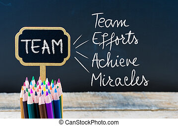 Business Acronym TEAM as Team Efforts Achieve Miracles written with chalk on wooden mini blackboard labels