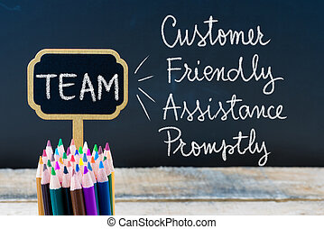 Business Acronym TEAM Customer Friendly Assistance Promptly written with chalk on wooden mini blackboard labels