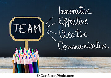 Business Acronym TEAM Innovative Effective Creative Communicative written with chalk on wooden mini blackboard labels