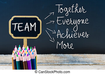 Business Acronym TEAM Together Everyone Achieves More written with chalk on wooden mini blackboard labels