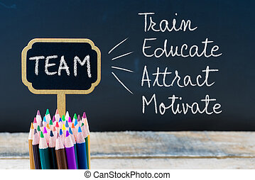 Business Acronym TEAM Train Educate Attract Motivate written with chalk on wooden mini blackboard labels