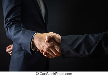 Business agreement and successful negotiation concept, businessman in suit shake hand with customer, client after formal communication and contract deal success on black background