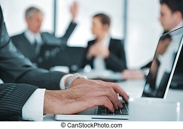 Business ambience, typing report on laptop during the meeting