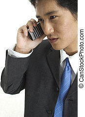 Business - An asian businessman talks business on the phone