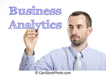 Business Analytics - Young businessman writing blue text on transparent surface