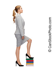 businesswoman stepping on pile of books - business and ...