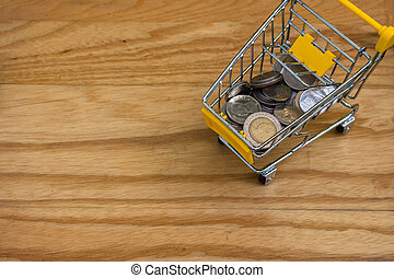 Business and Financial Concept : Top view of various money coins (Baht) in yellow mini shopping cart or supermarket trolley setting on wooden floor. (Selective focus)
