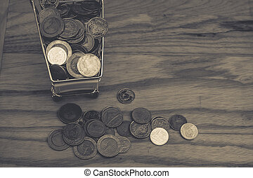 Business and Financial Concept : Various money coins (Baht) in yellow mini shopping cart or supermarket trolley beside pile of money coins on wooden table in vintage style. (Selective focus)