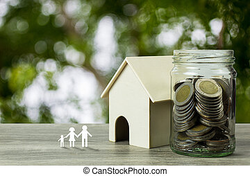 Business and financial property concept for home loan, mortgage, saving and investment. A small house model with stack of coins in glass jar and family in paper cut on wooden table.