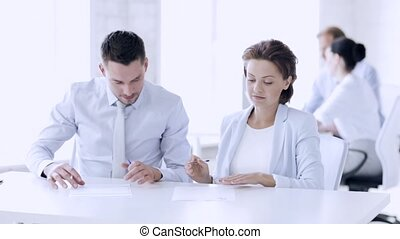 man and woman signing a contract