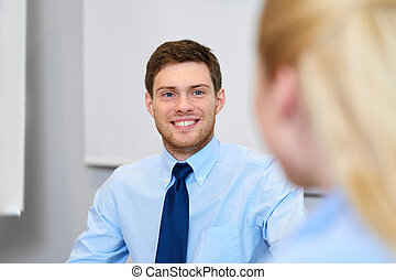 businessman talking to female colleague at office