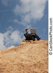 Business anywhere - Man sitting on a hilltop conducting ...