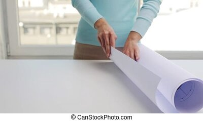 woman unwrapping architectural blueprint - business,...