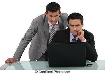 Business associates reading a distressing e-mail