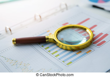 business audit - magnifying glass on financial graph report