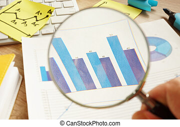 Business audit. Man is looking through magnifying glass on financial charts.