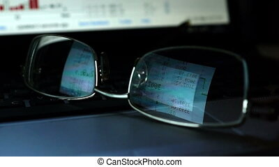 Glasses with reflection of stock trading data on a laptop keyboard.
