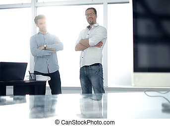 business background. two employees standing in a modern office.