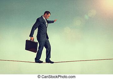 business balance - courageous businessman balancing on a...