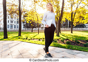 business beautiful girl walking in the park with a laptop at sunset
