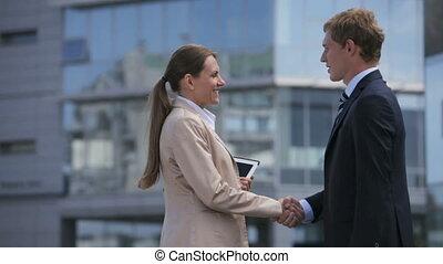 Elegant business woman and her colleague establishing business bonds