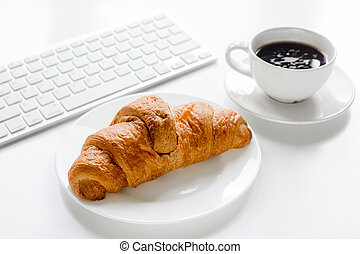 Business breakfast in office with keyboard, coffee and croissant on white table background