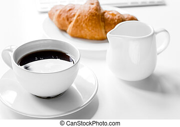 Business breakfast in office with milk, coffee and croissant on