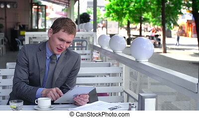 Business Breakfast - Businessman surfing the net on touchpad...