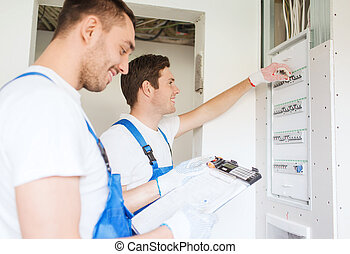 builders with clipboard and electrical panel - business,...