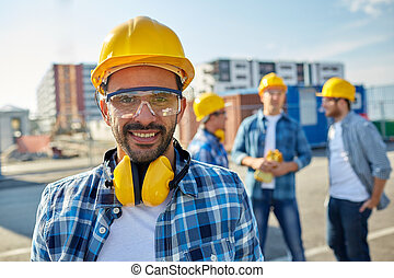 smiling builder with hardhat and headphones