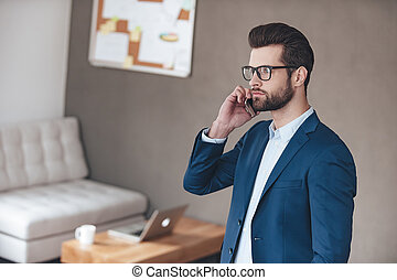 Business call. Handsome young man wearing glasses talking on mobile phone and looking away while standing in office
