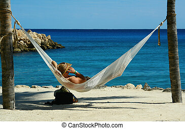 Business call - Man relaxed in a hammock on a tropical beach...