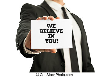 Businessman in a suit holding up a business card with motivational message We believe in you.