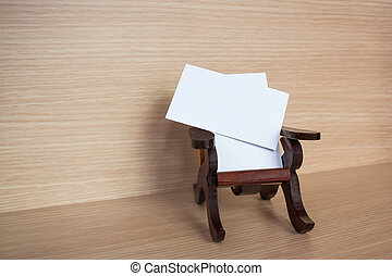 Business cards on a wooden chair.