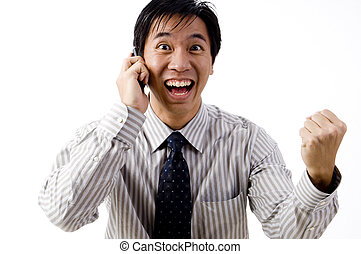 A young asian businessman celebrates his success on the phone