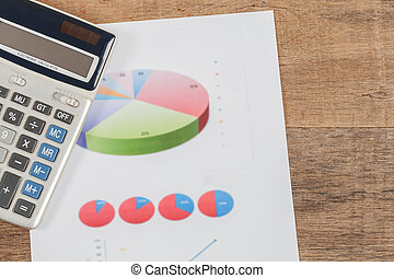 business chart and calculator on wooden desk