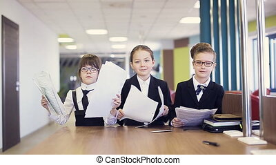 business children throw documents in air at office