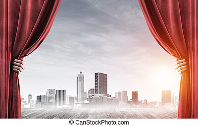 Business city behind red curtain and hand holding it