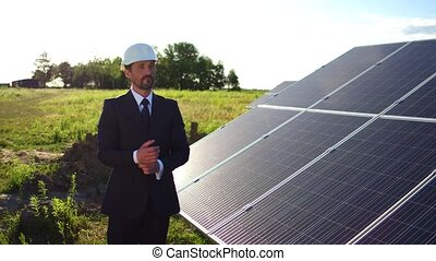 Business client at solar energy station, looking at photovoltaic panels,