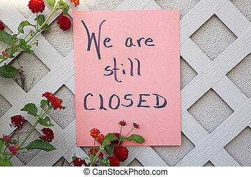 Business closed sign on orange paper on wall and trellis